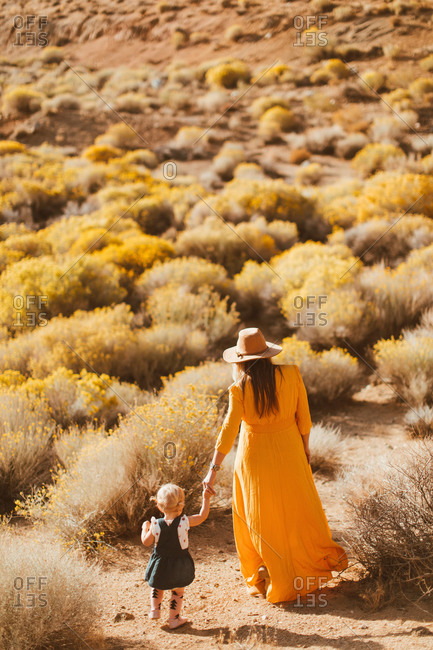 Mother and baby girl walking hand in hand, Kennedy Meadows, California, US