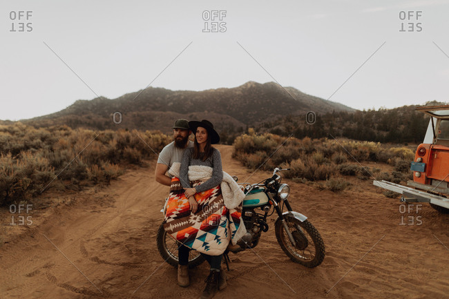 Couple relaxing on motorbike, Kennedy Meadows, California, US