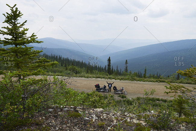 Senior male motorcyclist waving from rural mountain roadside with motorbike, high angle portrait, Dawson Creek, Canada