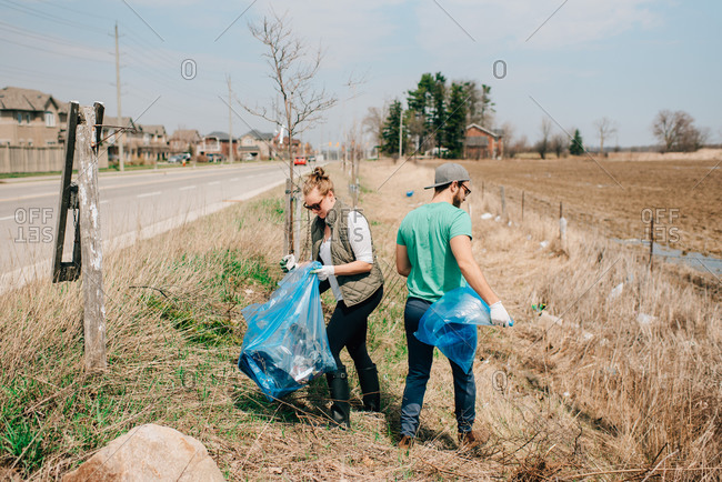 Couple picking up rubbish by roadside, Georgetown, Canada