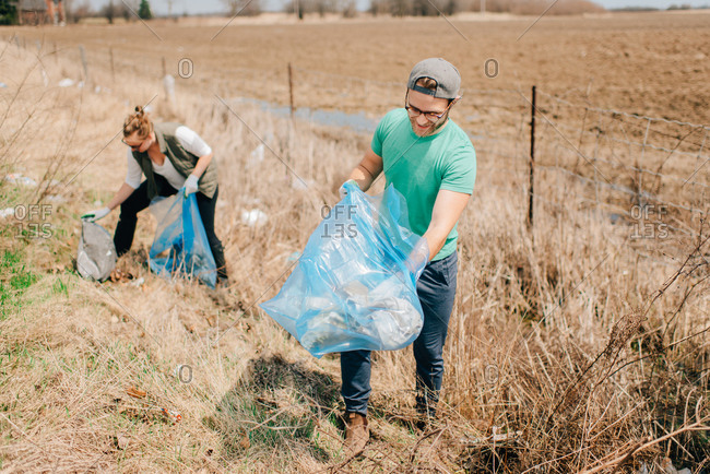 Couple picking up rubbish by field, Georgetown, Canada