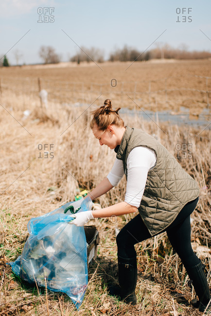 Woman picking up rubbish by field, Georgetown, Canada