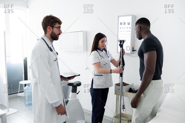 Doctor watching nurse examine patient in consultation room