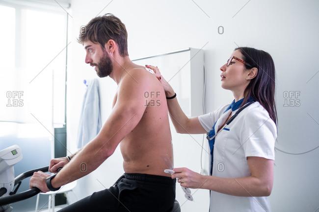 Nurse performing ECG test on patient in consultation room