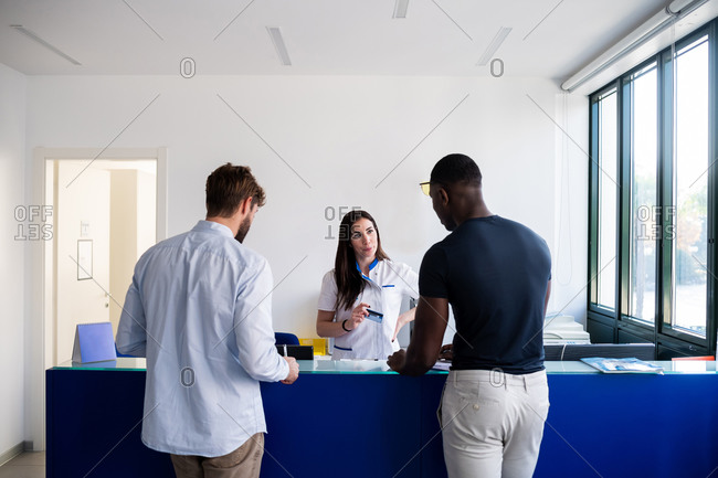 Nurse speaking with patients at hospital reception