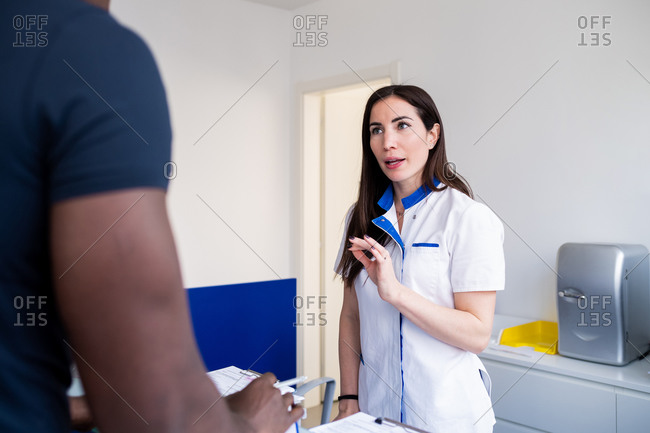 Nurse speaking with patient at hospital reception