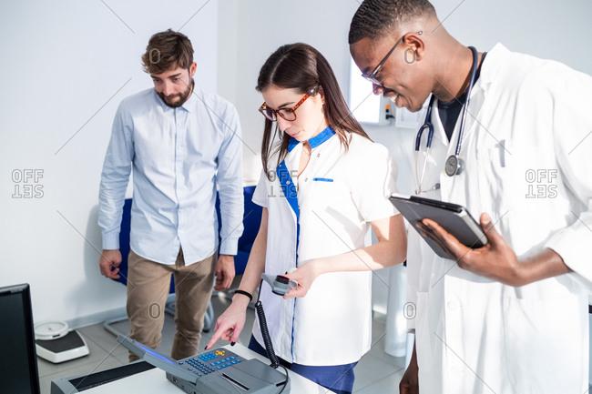 Doctors checking breathalyzer machine in hospital
