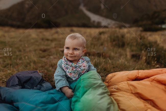 Baby sitting among jackets in wilderness, Wanaka, Taranaki, New Zealand