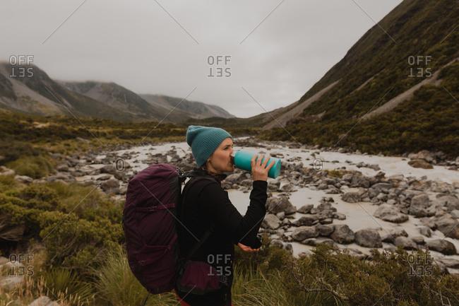 Hiker drinking, enjoying view of wilderness, Wanaka, Taranaki, New Zealand