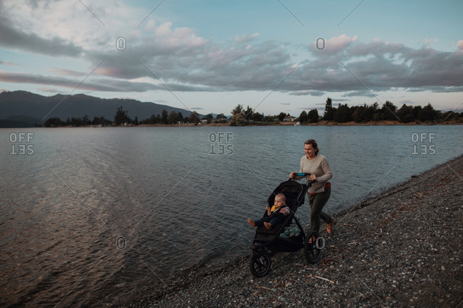 Mother with baby in pram walking on beach, Te Anau, Southland, New Zealand