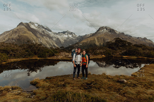 Hiker couple with baby by lake, Queenstown, Canterbury, New Zealand
