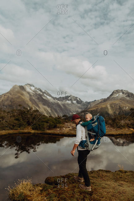 Hiker with baby by lake, Queenstown, Canterbury, New Zealand