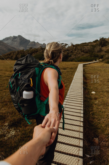 Hiker holding friend's hand on trail path, Queenstown, Canterbury, New Zealand