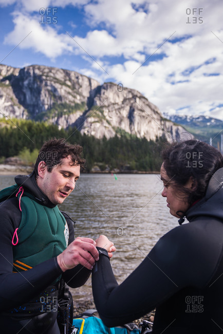 Man helping woman with wetsuit, Squamish, Canada