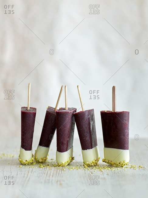 Tri-colored ice lollies in a row on table, white background