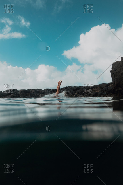 Swimmer diving off rocks into sea, Princeville, Hawaii, US