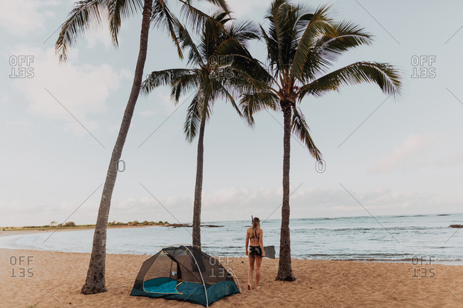 Scuba diver by tent on sandy beach, Princeville, Hawaii, US