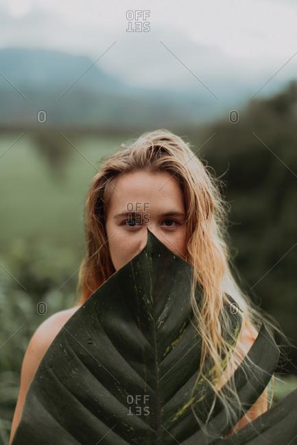 Woman in bikini holding large leaf, Princeville, Hawaii, US