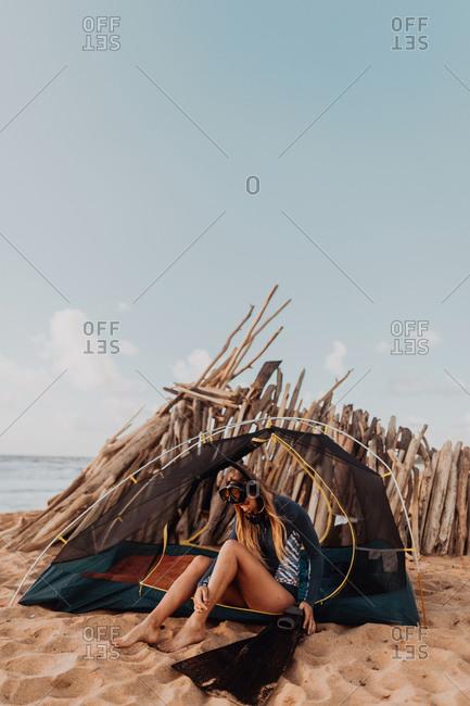 Scuba diver camping on sandy beach, Princeville, Hawaii, US