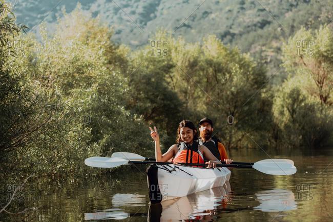 Friends taking break, showing peace sign in kayak, Kaweah, California, United States