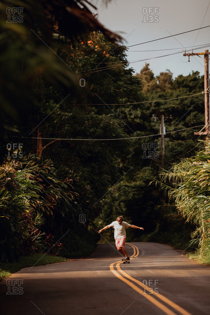 Mid adult male skateboarder skateboarding on centerline along rural road, Haiku, Hawaii, USA