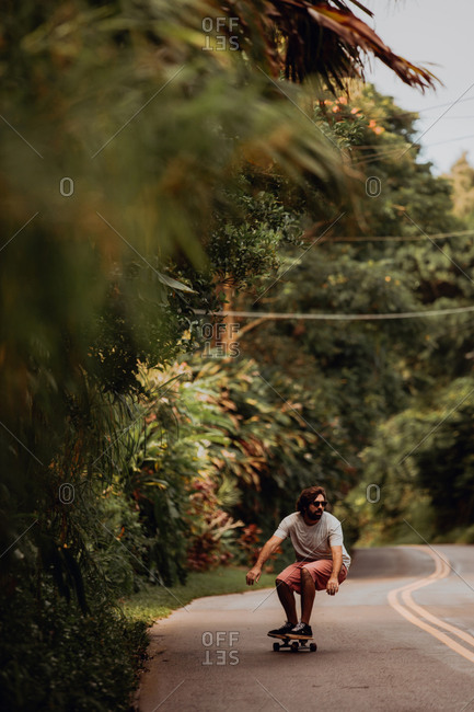 Mid adult male skateboarder crouching while skateboarding along rural road, Haiku, Hawaii, USA