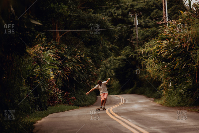 Mid adult male skateboarder skateboarding along rural road with arms outstretched, Haiku, Hawaii, USA