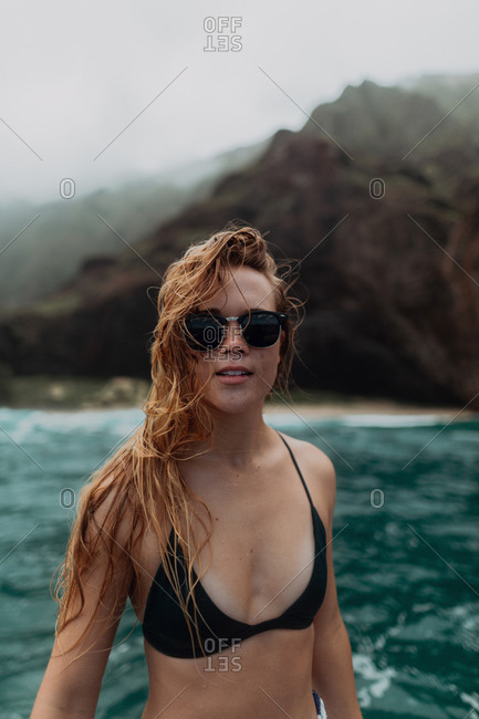 Woman in sunglasses and bikini by seaside, mountains in background, Princeville, Hawaii, US