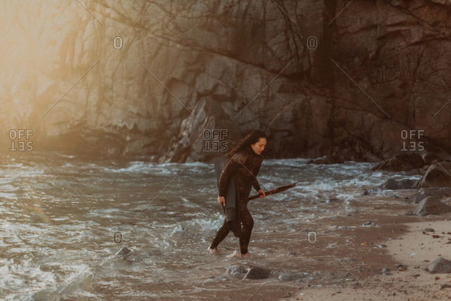 Woman with flippers and speargun on beach, Big Sur, California, United States