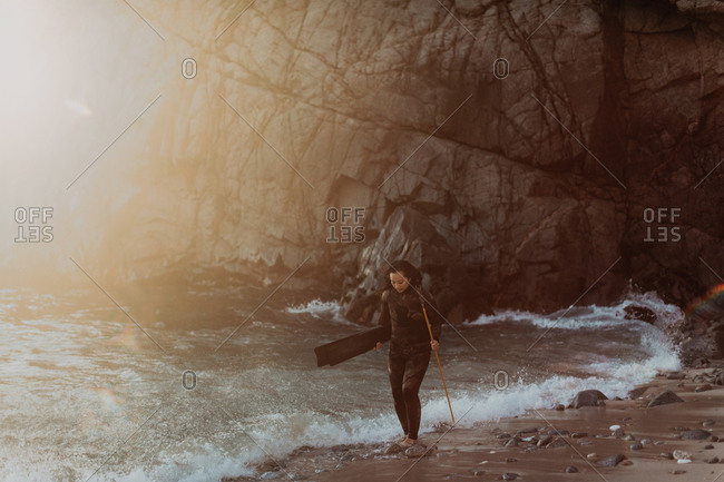 Woman with flippers and spear on beach, Big Sur, California, United States