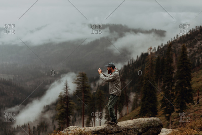 Hiker taking photograph of view of fog covering valley, Yosemite National Park, California, United States