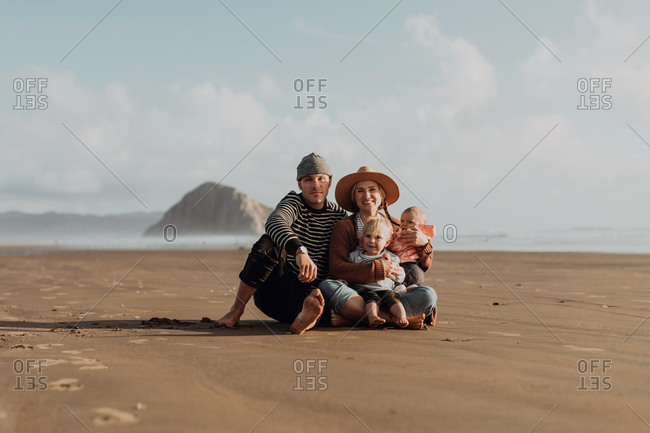 Parents and children sitting on beach, Morro Bay, California, United States