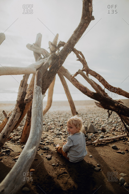 Toddler sitting inside wickiup on beach