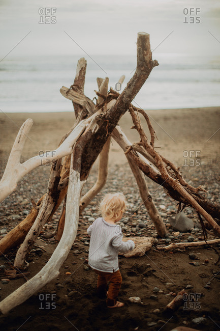 Toddler playing beside wickiup on beach