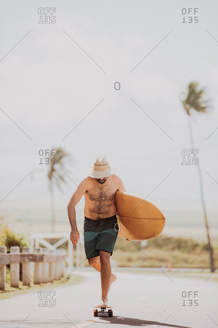 Mid adult male skateboarder carrying surfboard, skateboarding on coastal road, Haiku, Hawaii, USA