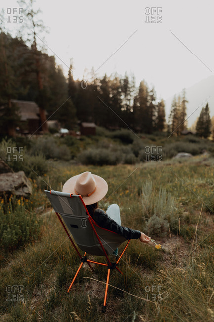Young woman in Stetson relaxing on deck chair in rural valley, rear view, Mineral King, California, USA