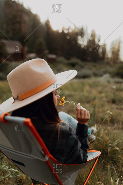 Young woman in Stetson smelling wildflower on deck chair in rural valley, rear view, Mineral King, California, USA