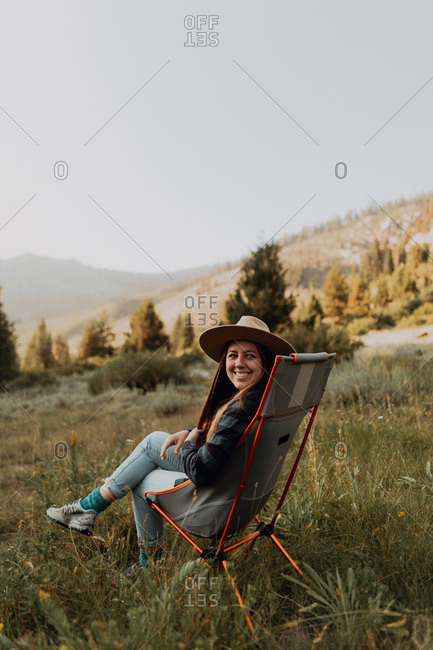 Young woman looking back from deck chair in rural valley, portrait, Mineral King, California, USA