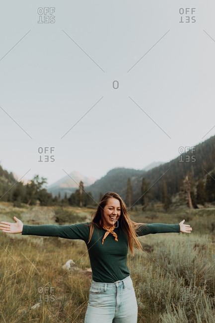 Young woman standing with open arms in rural valley, Mineral King, California, USA