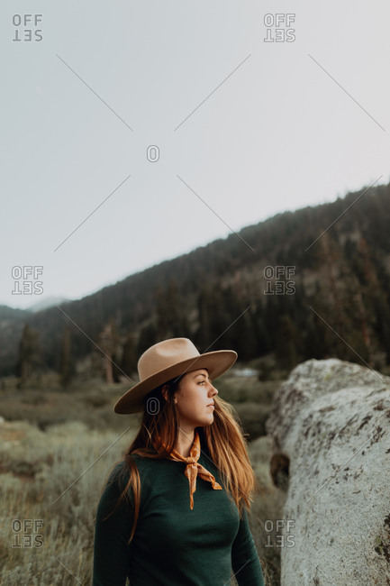 Young woman in Stetson looking over boulder in rural valley, Mineral King, California, USA