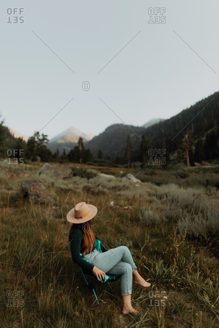 Young woman in Stetson relaxing on deckchair in rural valley, Mineral King, California, USA