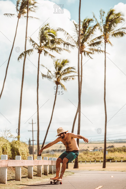 Mid adult male skateboarder wearing straw hat, skateboarding on coastal road, Haiku, Hawaii, USA