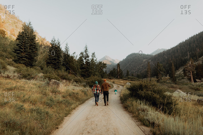 Mid adult couple following toddler daughter walking on rural valley road, rear view, Mineral King, California, USA