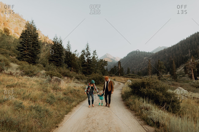 Mid adult couple walking with toddler daughter on rural valley road, Mineral King, California, USA