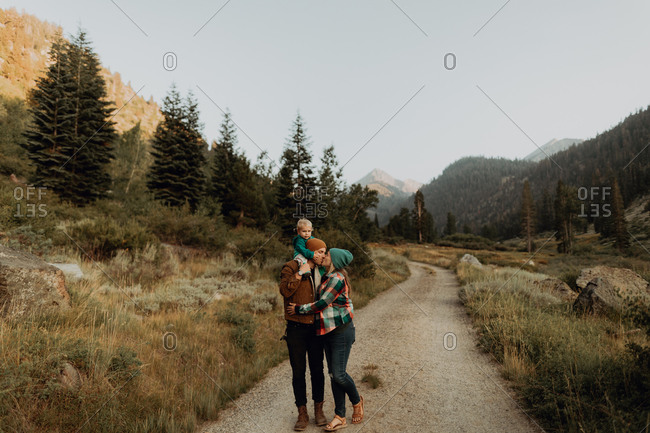 Mid adult couple with toddler daughter kissing on rural valley road, Mineral King, California, USA