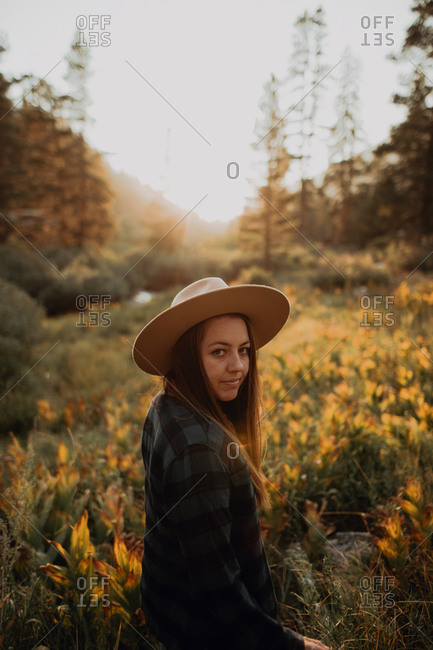 Young woman in Stetson looking back in rural valley at sunset, Mineral King, California, USA
