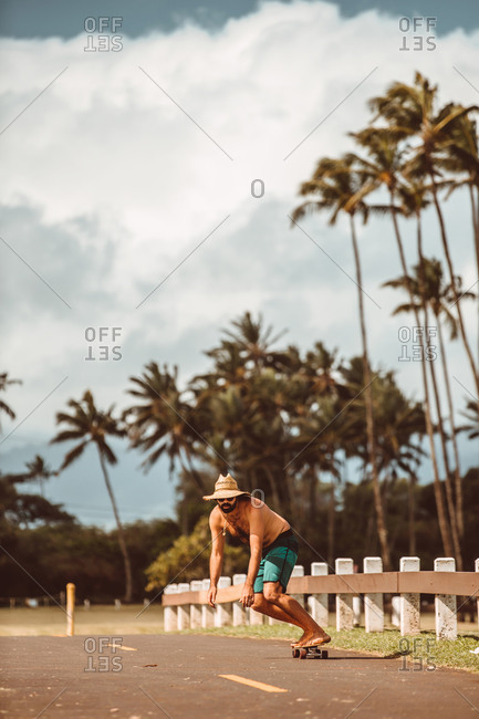 Mid adult male skateboarder wearing straw hat skateboarding on rural road, Haiku, Hawaii, USA
