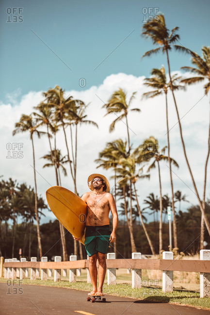 Mid adult male skateboarder wearing straw hat, standing on skateboard carrying surfboard on rural road, portrait, Haiku, Hawaii, USA