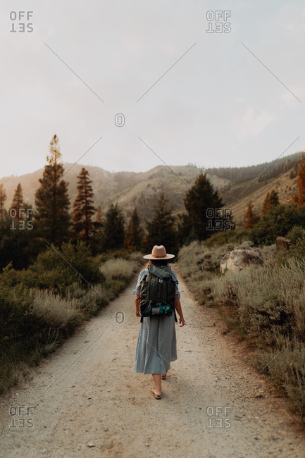 Young woman in maxi dress wearing backpack walking along rural road, rear view, Mineral King, California, USA