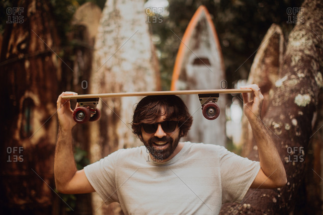 Mid adult male skateboarder carrying skateboard on head by old surfboard structure in park, portrait, Haiku, Hawaii, USA